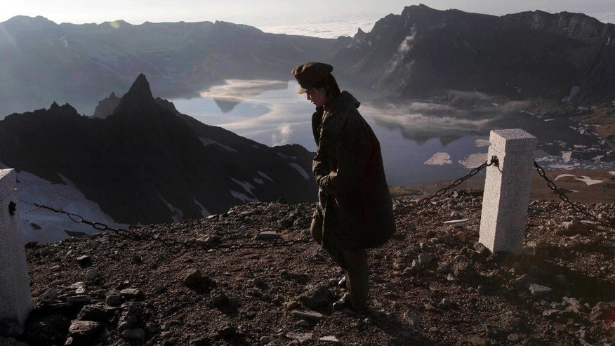 In this Wednesday, June 18, 2014 photo, a North Korean woman walks on the peak of Mt. Paektu in North Korea's Ryanggang province. More than a thousand years ago, a huge volcano straddling the border between North Korea and China was the site of one of the biggest eruptions in human history, blanketing eastern Asia in its ash. But unlike other major volcanos around the world, the remote and politically sensitive Mount Paektu remains almost a complete mystery to foreign scientists who have - until recently - been unable to conduct on-site studies. (AP Photo/David Guttenfelder)