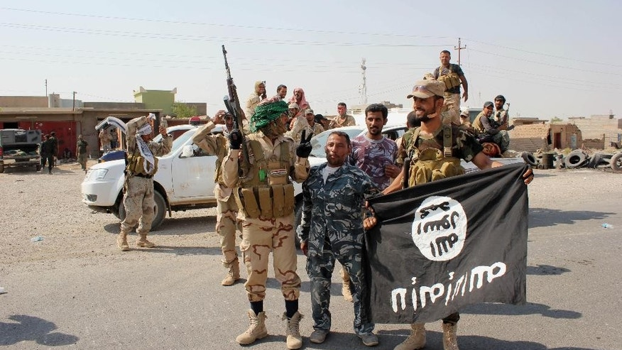 "In this Monday, Sept. 1, 2014 photo, Shiite militiamen hold the flag of the Islamic State group they captured, during an operation outside Amirli, some 105 miles (170 kilometers) north of Baghdad, Iraq. Under the shadow of the Islamic State group threat, governments from France to Indonesia are moving aggressively to block would-be jihadis from taking their fight to Syria and Iraq. New laws make it easier to seize passports. Suspected fighters are being plucked from planes. Authorities are blocking finances and shutting down radical mosques. Behind the scenes, Western intelligence agencies are striving to stay ahead of tech-savvy radicalized Muslims by pressuring Silicon Valley firms to wipe extremist content from websites and toying with new technologies to identify returning fighters at the border. Britain has taken a particularly active role in censoring content deemed to break the country's strict rules against extremist propaganda. U.K. officials recently revealed it had been granted ""super flagger"" status on sites such as YouTube, meaning their requests to remove videos with grisly content or that encourage terrorism are fast-tracked. (AP Photo)"