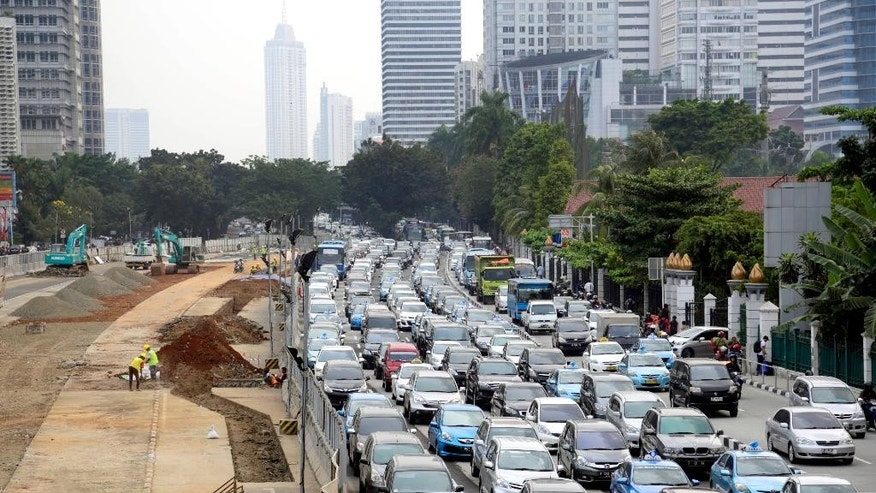 In this Friday, Aug. 29, 2014 photo, cars line up in a traffic congestion next to Mass Rapid Transit (MRT) construction site on the left, in Jakarta, Indonesia. The first item on the to-do list of Indonesia's next president is one that successive leaders have struggled with, and could be his toughest: how to wean the country off fuel subsidies that make gasoline almost as cheap as bottled water. (AP Photo/Dita Alangkara)