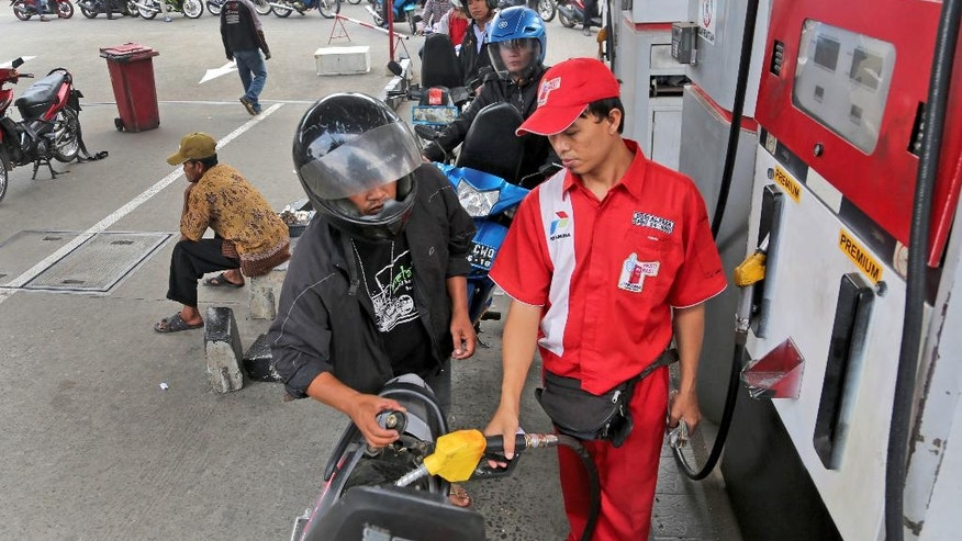 In this Sept. 1, 2014 photo, an attendant fills up the tank of a motorbike at a gas station in Jakarta, Indonesia. The first item on the to-do list of Indonesia's next president is one that successive leaders have struggled with, and could be his toughest: how to wean the country off fuel subsidies that make gasoline almost as cheap as bottled water. Each year the subsidies cost Indonesia billions of dollars that economists agree would be better spent on creating jobs and building badly needed roads, schools and hospitals in Southeast Asia's largest economy. (AP Photo/Tatan Syuflana)