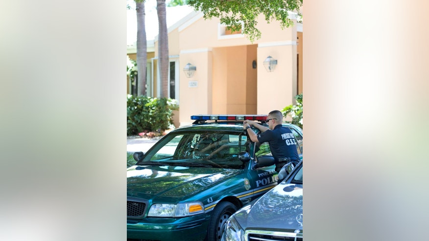 A Pinecrest, Fla., police officer stands outside the home of the family of journalist Steven Sotloff, Tuesday, Sept. 2, 2014 in Pinecrest, Fla. An Internet video posted online Tuesday purported to show the beheading by the Islamic State group of Sotloff, who went missing in Syria last year. The extremist group, which has claimed wide swaths of territory across Syria and Iraq and declared itself a caliphate, said Sotloff's killing was retribution for continued U.S. airstrikes targeting its fighters in Iraq. (AP Photo/Wilfredo Lee)