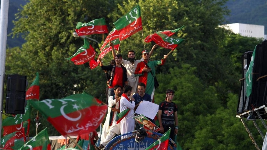 Supporters of Pakistan's cricketer-turned-politician Imran Khan wave party flags as they chant slogans during a protest near Prime Minister's home in Islamabad, Pakistan, Tuesday, Sept. 2, 2014. Anti-government demonstrators led by opposition politician Khan and Tahir-ul-Qadri converged on the capital in mid-August, demanding Sharif's ouster over alleged fraud in last year's election. Their protests turned violent this past weekend, when clashes between demonstrators and security forces killed many and wounded hundreds. (AP Photo/Anjum Naveed)