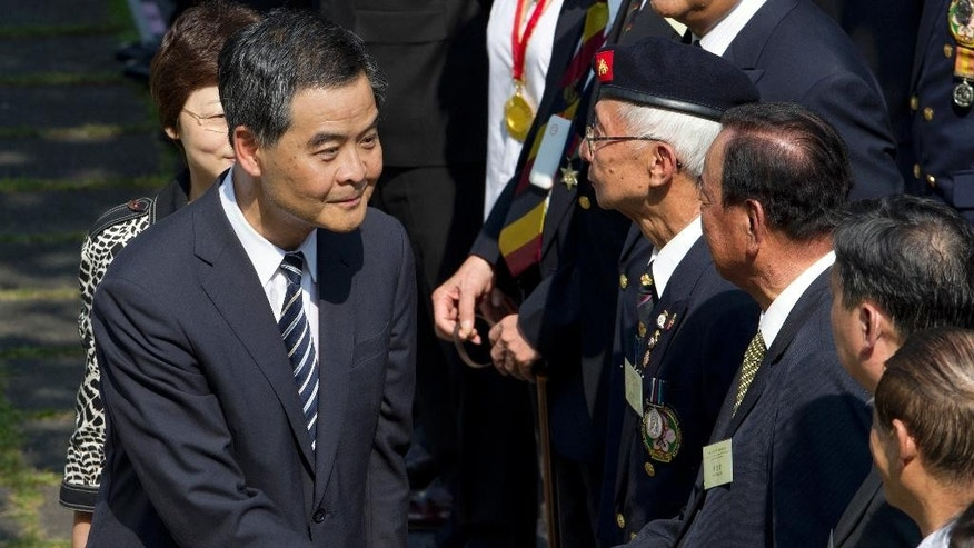 Hong Kong's Chief Executive Leung Chun-ying, left, shakes hands with Lau Wong-fat, a member of the Hong Kong Legislative Council, after a ceremony to mark the 69th anniversary of China's World War II victory over Japan, in Hong Kong Wednesday, Sept. 3, 2014. It's the first official ceremony to be held annually after the National People's Congress Standing Committee designated Sept. 3 as a commemoration day. (AP Photo/Vincent Yu)