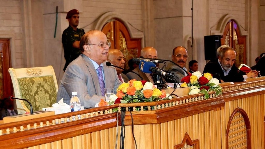 In this photo provided by Yemen's Defense Ministry, Yemeni President Abed Rabbo Mansour Hadi, left, speaks to members of the government and the parliament during a meeting in Sanaa, Yemen, Tuesday, Sept. 2, 2014. The Yemeni president on Tuesday dismissed the Cabinet including the prime minister who led it for two years, while partially reversing an earlier decision to lift fuel subsidies in a bid to end a standoff with Shiite rebels holding anti-government protests across the country. (AP Photo/Yemen's Defense Ministry)