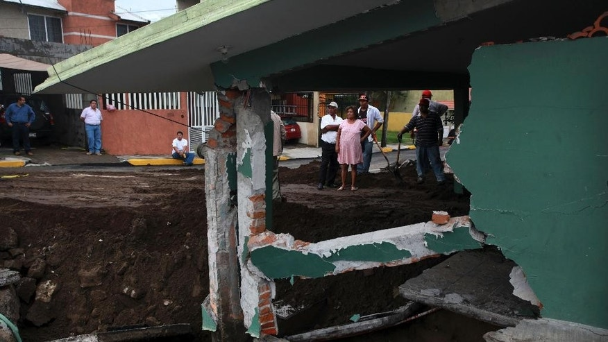 Neighbors look at the damage after part of a street and a home collapsed due to heavy rains in the Gulf port city of Veracruz, Mexico, Tuesday Sept. 2, 2014. The Gulf states of Mexico are bracing for more bad weather as Tropical Storm Dolly will cross the coast lat this evening or overnight and continue moving inland over northeastern Mexico on Wednesday. (AP Photo/Felix Marquez)