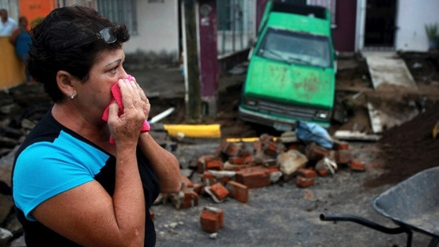Maria del Carmen Gonzalez watches after part of a street and her home collapsed due to heavy rains in the Gulf port city of Veracruz, Mexico, Tuesday Sept. 2, 2014. The Gulf states of Mexico are bracing for more bad weather as Tropical Storm Dolly will cross the coast lat this evening or overnight and continue moving inland over northeastern Mexico on Wednesday. (AP Photo/Felix Marquez)