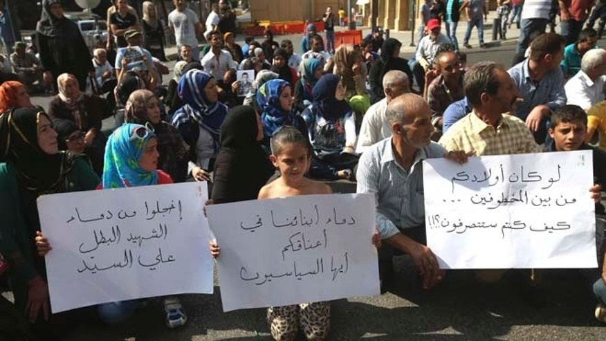 """Sept. 4, 2014: Families of missing soldiers who were kidnapped by Islamic State militants and the Al-Nusra front, sit on the ground street as they hold Arabic banners that read: """"you should be ashamed of the blood of the hero martyr Ali Sayid (the beheaded Lebanese soldier),"""" left, """"Hey politicians the blood of our sons is in your hands,"""" center, and """"If your children were among those kidnapped ... what would you have done?"""" right, during a demonstration to demand action to secure the captives' release, in front the Lebanese government building, in downtown Beirut, Lebanon. (AP)"""