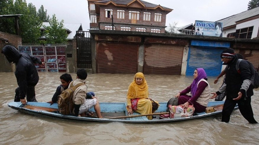 Sept. 4, 2014: Residents leave a flooded neighborhood on a boat in Srinagar, India. Authorities say heavy rains have triggered floods and landslides in the Indian portion of Kashmir, killing at least 14 people in the worst flooding in 22 years.
