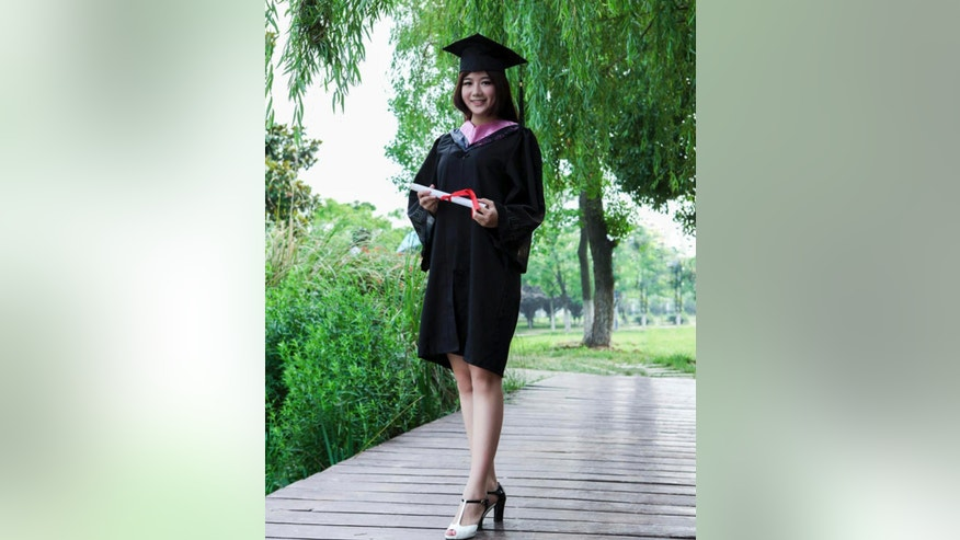 In this photo taken June 2014 and released by Liao Minyue, Liao Minyue poses for a graduation photo in central China's Anhui province. During her time in university, 22-year-old Liao was called in by school officials who criticized her mother's activism, and classmates were warned to keep an eye on her. (AP Photo/Liao Minyue)