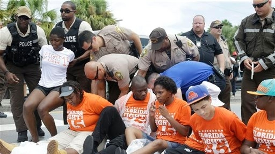 Police officers arrest demonstrators Thursday, Sept. 4, 2014 in North Miami Beach, Fla.