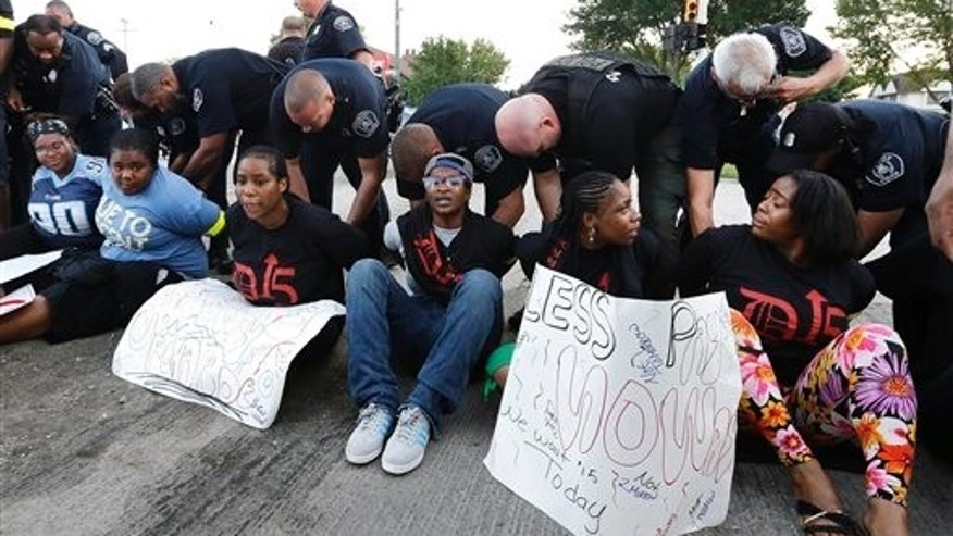 Police handcuff protesters blocking traffic on Mack Avenue in Detroit as part of a national protest to push fast-food chains to pay their employees at least $15 an hour Thursday, Sept. 4, 2014. Hundreds of workers from McDonald's, Taco Bell, Wendy's and other fast-food chains are expected to walk off their jobs Thursday, according to labor organizers of the latest national protest to push the companies to pay their employees at least $15 an hour. (AP Photo/Paul Sancya)