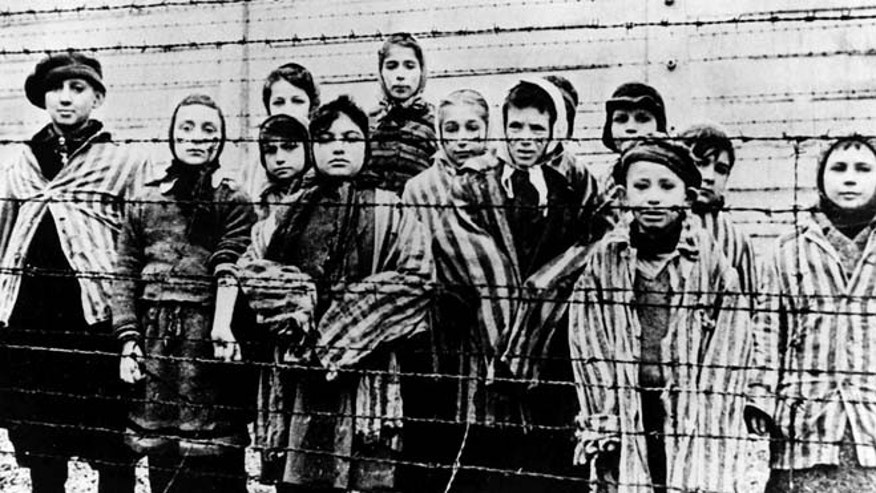 The file picture taken just after the liberation by the Soviet army in January, 1945 shows a group of children wearing concentration camp uniforms including Martha Weiss who was ten years-old, 6th from right, at the time behind barbed wire fencing in the Oswiecim (Auschwitz) Nazi concentration camp. (AP)