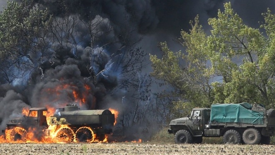 Sept. 4, 2014: Unmarked Military vehicles burning in country roads in the village of Berezove, eastern Ukraine, after a clash between pro-government troops and Russian-backed separatist militia. Separatist rebels have made major strides in their offensive against Ukrainian government forces in recent days, drawing on what Ukraine and NATO says is ample support from the Russian military.