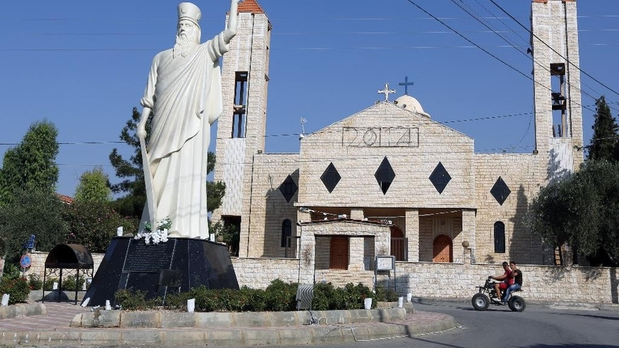 In this Wednesday, Aug. 13, 2014 photo, two young men ride a motorcycle past a church in Lebanon's Christian village of Ras Baalbek in the northern Bekaa region near the border with Syria. Across the Middle East, Christian communities as old as the religion itself feel their very survival is at stake, threatened by militants of the Islamic State group rampaging across Iraq and Syria. Many Christian villagers are setting up self-defense units to protect themselves against attack. In Qaa and Ras Baalbek, two Christian northeastern villages on the border with Syria, many of the thousands of expatriates who used to spend the summer there stayed away this year. (AP Photo/Bilal Hussein)