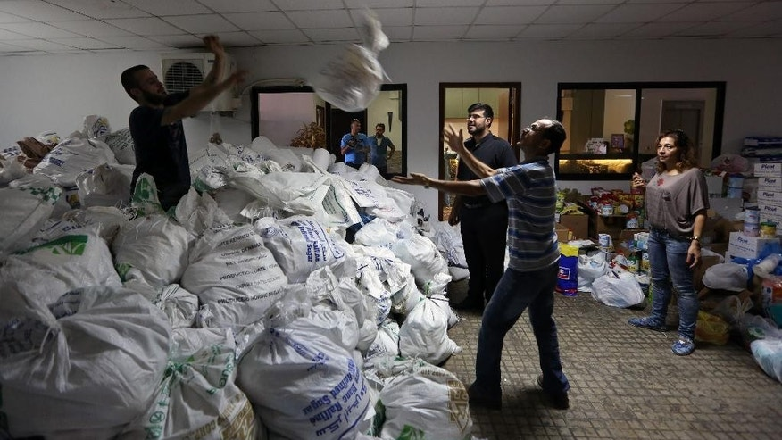 In this Wednesday, Aug. 20, 2014 photo, Christian volunteers distribute food and clothes to Iraqis who fled their homes in Iraq and came to Lebanon, at the Chaldean Diocese in Baabda, east of Beirut, Lebanon. Across the Middle East, Christian communities as old as the religion itself feel their very survival is at stake, threatened by militants of the Islamic State group rampaging across Iraq and Syria. For months, Lebanese Christians have watched with dread as their co-religionists flee Islamic extremists in Syria and Iraq, fearing their turn will come next. (AP Photo/Bilal Hussein)