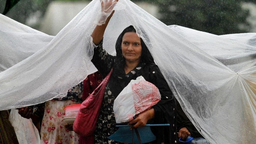 A Pakistani protester uses plastic sheet to cover herself from rain as she moves to another place at the premises of parliament building where they camped in Islamabad, Pakistan on Thursday, Sept. 4, 2014. Negotiators for thousands of protesters demonstrating outside of Pakistan's parliament met with politicians trying to end the crisis, but key challenges appear to remain — including their demand that the prime minster resign. (AP Photo/Anjum Naveed)