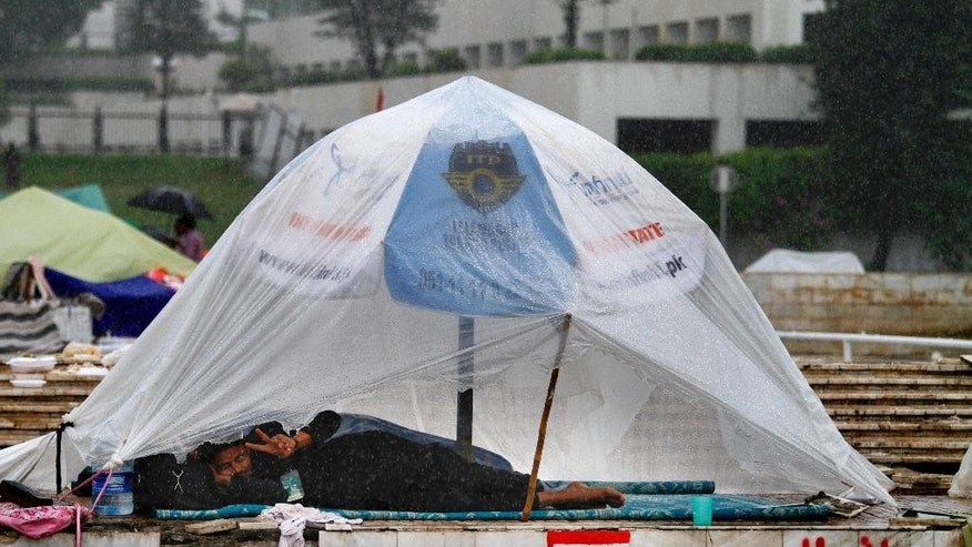 A Pakistani protester flashes a victory sign in a tent setup with plastic sheet to shield himself from rain at the premises of parliament building in Islamabad, Pakistan on Thursday, Sept. 4, 2014. Negotiators for thousands of protesters demonstrating outside of Pakistan's parliament met with politicians trying to end the crisis, but key challenges appear to remain - including their demand that Prime Minister Nawaz Sharif resign. (AP Photo/Anjum Naveed)