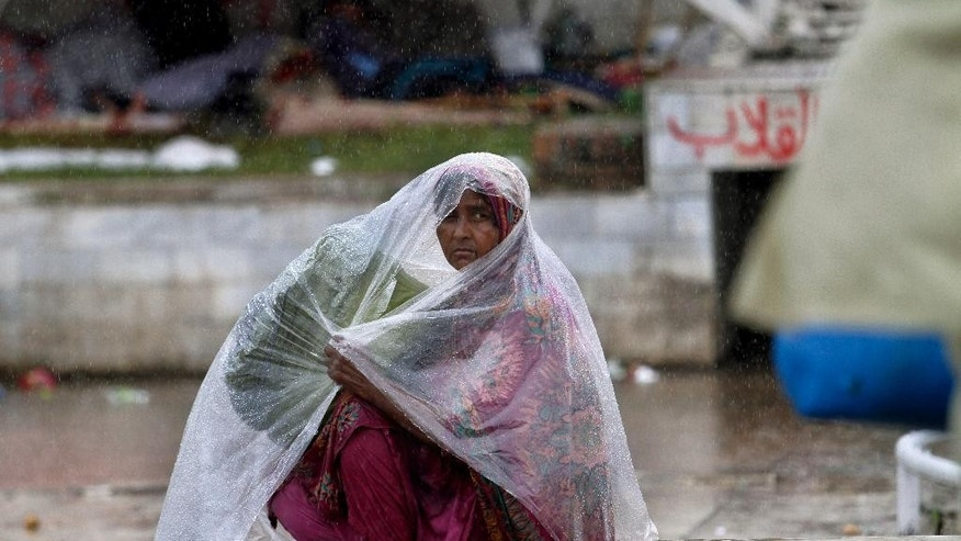 A Pakistani protester wraps a plastic sheet to cover herself from rain as she and others camped at the premises of parliament building in Islamabad, Pakistan on Thursday, Sept. 4, 2014. Negotiators for thousands of protesters demonstrating outside of Pakistan's parliament met with politicians trying to end the crisis, but key challenges appear to remain - including their demand that Prime Minister Nawaz Sharif resign. (AP Photo/Anjum Naveed)