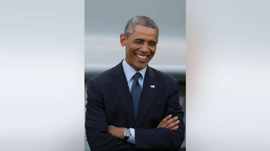 U.S. President Barack Obama smiles during a flypast at the NATO summit at the Celtic Manor Resort in Newport, Wales on Friday, Sept. 5, 2014. (AP Photo/Jon Super)