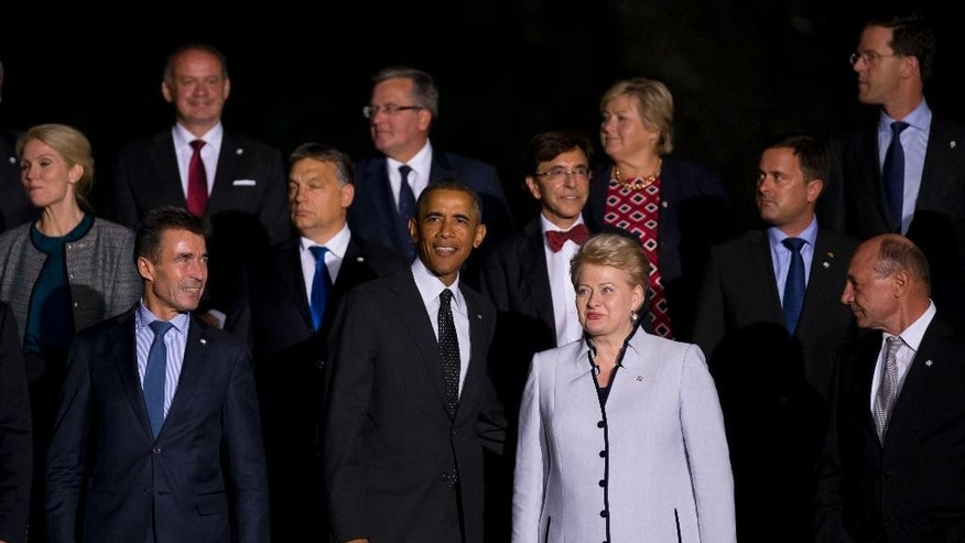 U.S. President Barack Obama, front row center, stands with NATO heads of state and government including Lithuanian President Dalia Grybauskaite, front row centre right, and NATO Secretary General Anders Fogh Rasmussen, front left, as they pose for a group photo prior to a NATO summit dinner at Cardiff Castle in Cardiff, Wales on Thursday, Sept. 4, 2014. In a two-day summit leaders will discuss, among other issues, the situation in Ukraine and Afghanistan. (AP Photo/Jon Super)