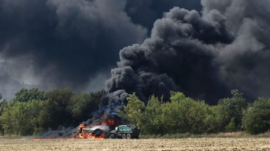 Sept. 4, 2014: Unmarked military vehicles burn on a country road in the village of Berezove, eastern Ukraine after a clash between pro-government troops and Russian-backed separatist militia.