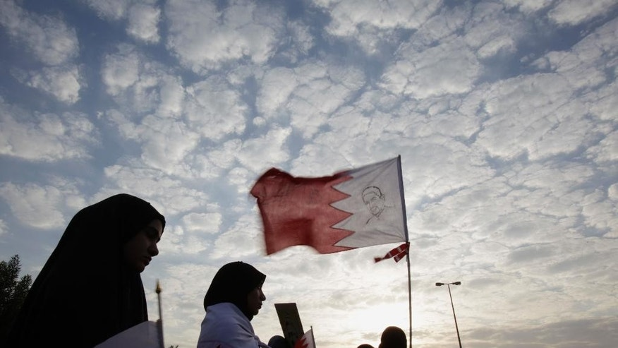 Protesters against the Bahraini government carry national flags, including one with an image of Abdulhadi al-Khawaja, a jailed activist who is on hunger strike to protest his detention, during a march in Shakhoora, Bahrain, Friday, Sept. 5, 2014. A few thousand Bahrainis turned out for the march, demanding freedom for al-Khawaja and others jailed during the past 3 1/2 years of protests against the Gulf island monarchy. (AP Photo/Hasan Jamali)