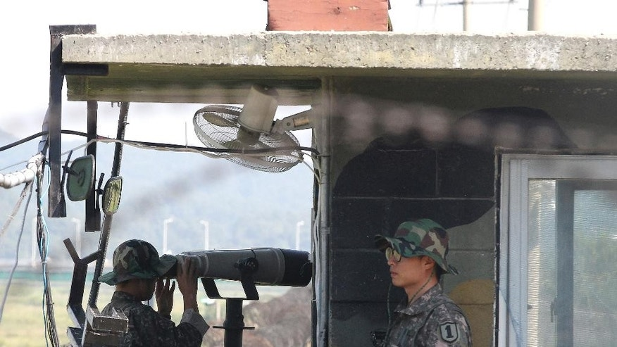A South Korean army soldier looks through a pair of binoculars at a military check point in Paju near the border with North Korea, South Korea, Saturday, Sept. 6, 2014. North Korea on Saturday continued its string of rocket and missile firings, launching three short-range projectiles into the waters off its east coast ahead of a major holiday celebrated by both Koreas, a South Korean defense official said. (AP Photo/Ahn Young-joon)