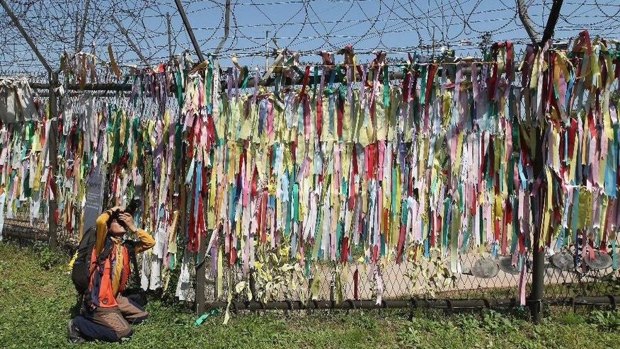 A man takes souvenir photos in front of a wire fence decorated with ribbons carrying messages visitors left, wishing for the reunification of the two Koreas, at the Imjingak Pavilion in Paju near the border with North Korea, South Korea, Saturday, Sept. 6, 2014. North Korea on Saturday continued its string of rocket and missile firings, launching three short-range projectiles into the waters off its east coast ahead of a major holiday celebrated by both Koreas, a South Korean defense official said. (AP Photo/Ahn Young-joon)