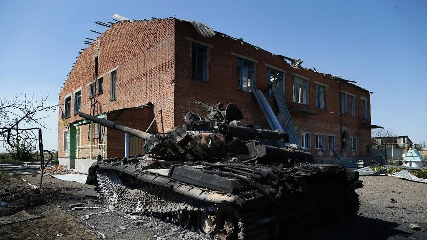 A burned Ukrainian army tank is seen near a destroyed kindergarten in the village of Kominternove, Ukraine, Saturday, Sept. 6, 2014. After four months of war, eastern Ukraine begins the first full day of an uncertain cease-fire. The truce agreement calls for an exchange of prisoners and establishment of humanitarian corridors, but how quickly those actions will begin is unclear. (AP Photo/Sergei Grits)
