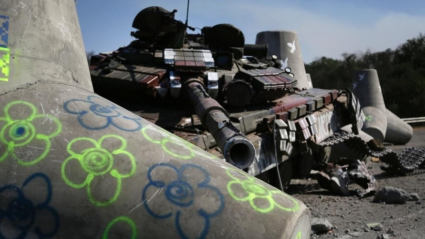 A destroyed Ukrainian army tank is seen near the village of Lebedynske, on the highway joining Mariupol and Novoazovsk, Saturday, Sept. 6, 2014. After four months of war, eastern Ukraine begins the first full day of an uncertain cease-fire. The truce agreement calls for an exchange of prisoners and establishment of humanitarian corridors, but how quickly those actions will begin is unclear.(AP Photo/Sergei Grits)