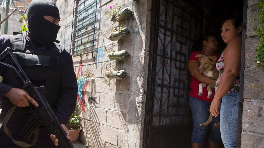 In this Aug. 22, 2014 photo, a masked National Police officer patrols as residents step back into their homes in the Mejicanos neighborhood as police search for weapons in San Salvador, El Salvador. A truce declared two years ago by the gangs Mara Salvatrucha and the 18th Street Gang briefly tapered their bloody gang war, but the cease-fire had an unintended consequence: It gave the gangs breathing room to grow even stronger. Now, violence is on the rise again. (AP Photo/Esteban Felix)
