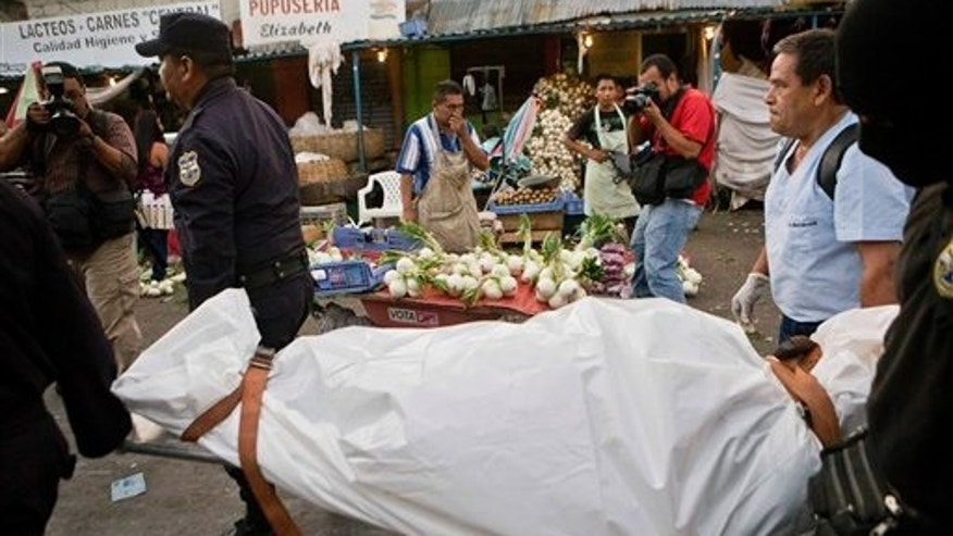 In this Aug. 23, 2014 photo, police and forensic workers carry away the body of the man who was shot to death at the Central Market of San Salvador, El Salvador. The victim was shot in the head by two men while working as a waiter at a restaurant inside the market, according to police at the scene. A truce declared two years ago by the gangs Mara Salvatrucha and the 18th Street Gang briefly tapered their bloody gang war, but the cease-fire had an unintended consequence: It gave the gangs breathing room to grow even stronger. Now, violence is on the rise again. (AP Photo/Esteban Felix)