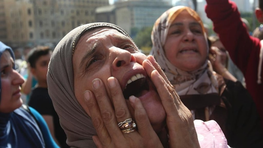 This Thursday, Sept. 4, 2014, the mother of a missing Lebanese soldier who was kidnapped by Islamic State militants, shouts slogans against the Lebanese cabinet during a demonstration to demand action to secure the captives' release, in front the Lebanese government building, in downtown Beirut, Lebanon. The mother of Lebanese soldier Abbas Medlej, held captive by the militant Islamic State group says that photographs posted online purporting to show his beheading appear real, on Saturday, Sept. 6, 2014. Militants, including from the Islamic State extremist group, seized around 30 soldiers and policemen after overrunning a Lebanese border town in early August. (AP Photo/Hussein Malla, File)