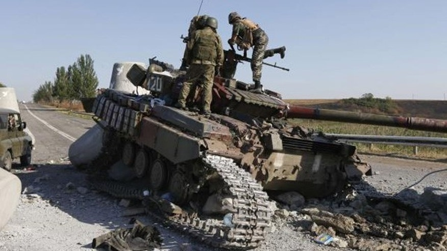 September 6, 2014: Ukrainian soldiers inspect a damaged tank on the outskirts of the southern coastal town of Mariupol. (REUTERS/VASILY FEDOSENKO)