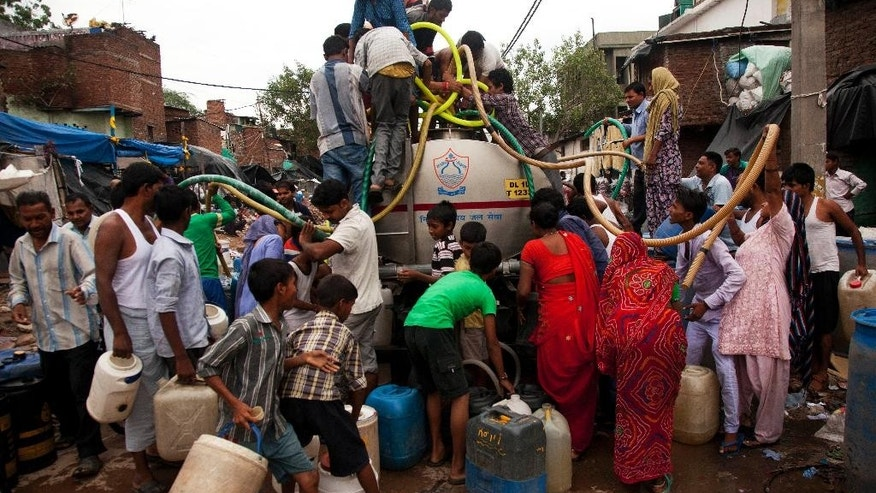 In this Tuesday, Sept. 2, 2014 photo, residents crowd around a government tanker delivering drinking water at a slum in New Delhi, India. In a city known for its vertiginous inequalities, water shortage affects people from both upscale gated communities and dust-blown slums, as every day, supply falls more than 160 million gallons short. The city's water agency, the Delhi Jal Board, sends 900 tankers onto the crowded roads every day. Tankers usually stop for just 15 minutes, while dozens of people crowd around waving buckets and plastic tubes, in some areas, people get just 3 liters. (AP Photo/Patrick Reevell)