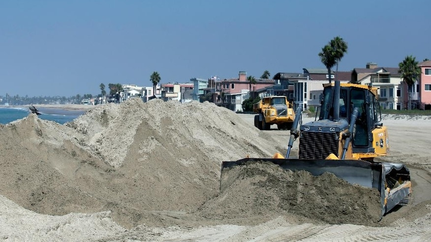 A bulldozer works to pile sand on a temporary berm to protect beach front homes on, Friday, Sept. 5, 2014, in Long Beach, Calif. Southern California is in for another round of high surf generated by what is currently Hurricane Norbert in the Pacific Ocean off Baja California. (AP Photo/Chris Carlson)