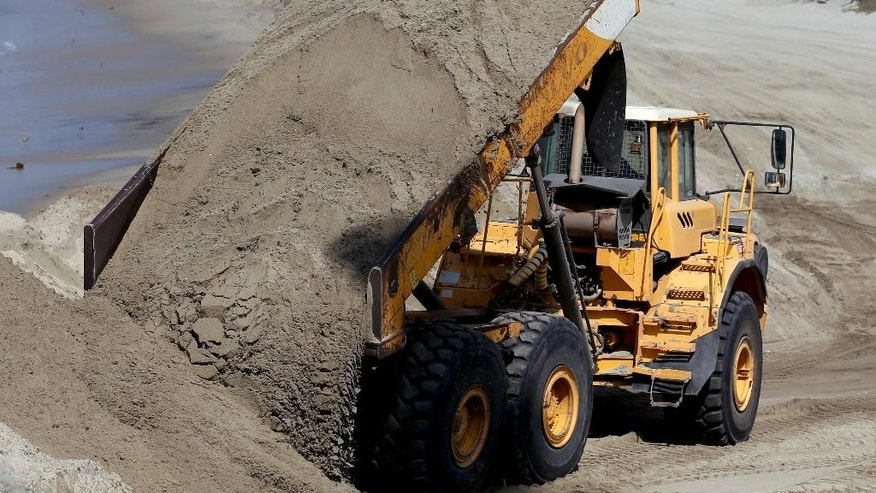 A dump truck works to pile sand on a temporary berm to protect beach front homes on, Friday, Sept. 5, 2014, in Long Beach, Calif. Southern California is in for another round of high surf generated by what is currently Hurricane Norbert in the Pacific Ocean off Baja California. (AP Photo/Chris Carlson)