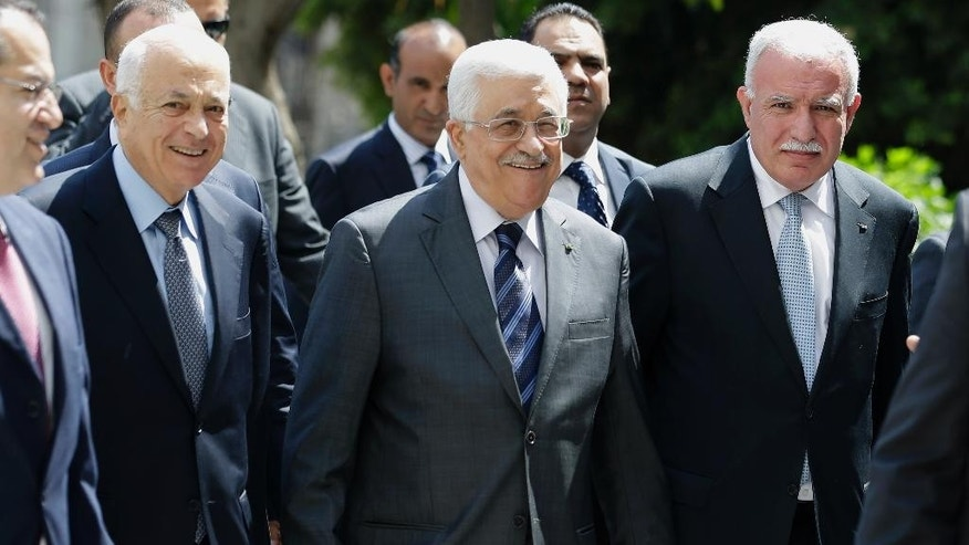Palestinian President Mahmoud Abbas, center, arrives with the Arab League's Secretary-General Nabil Elaraby, left, and Palestinian Foreign Minister Riyad al-Maliki to attend an Arab foreign minister meeting at the Arab League headquarters in Cairo, Egypt, Sunday, Sept. 7, 2014. Abbas threatened to dissolve a new unity government if the Hamas militant group does not yield power in the Gaza Strip. (AP Photo/Hassan Ammar)