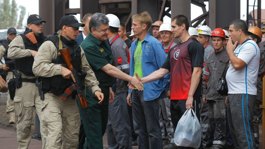 Sept. 8, 2014. - Ukrainian President Petro Poroshenko, center, greets workers during his visit to the Ilich Iron and Steel Works in Mariupol, Ukraine.Poroshenko made a surprise trip to southeastern Ukraine as a cease-fire between Russian-backed rebels and Ukrainian troops appeared to be largely holding.