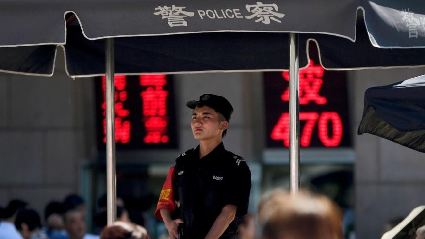 In this Wednesday, Sept. 3, 2014 photo, an armed policeman stands guard on a police booth at a crowded railway station in Beijing, China. Beijing's tight controls and monopoly on the narrative make it difficult to independently assess if the lethal action has been justified. And Chinese authorities prevent most reporting by foreign journalists inside Xinjiang, making it nearly impossible to confirm the state media numbers. Uighur exile groups and the U.S.-government funded broadcaster Radio Free Asia report far more violent incidents than Chinese state media do, and in some cases, higher death tolls and police shootings of Uighur protesters. But those reports are similarly hard to verify. (AP Photo/Andy Wong)