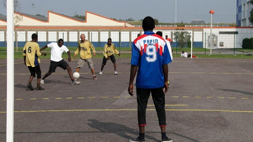 "Migrants play soccer in Calais, northern France, Sunday, Sept 7, 2014.. Hundreds of extreme-right activists demonstrated Sunday to ""save"" Calais from homeless migrants inundating the French port city in hopes of crossing the English Channel to Britain. (AP Photo/Michel Spingler)"