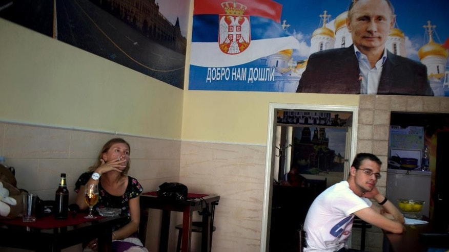 "In this photo taken Tuesday, Aug. 5, 2014, a woman smokes as she has a drink at the ""Putin Caffe"" in Novi Sad, Serbia. Serbia, caught in the middle of Moscow's row with the European Union and the United States over the crisis in Ukraine, is suddenly being confronted with a hard choice: continue on its proclaimed course toward the EU, or give up that goal and seek even closer ties with its traditional Slavic ally Russia. (AP Photo/Marko Drobnjakovic)"