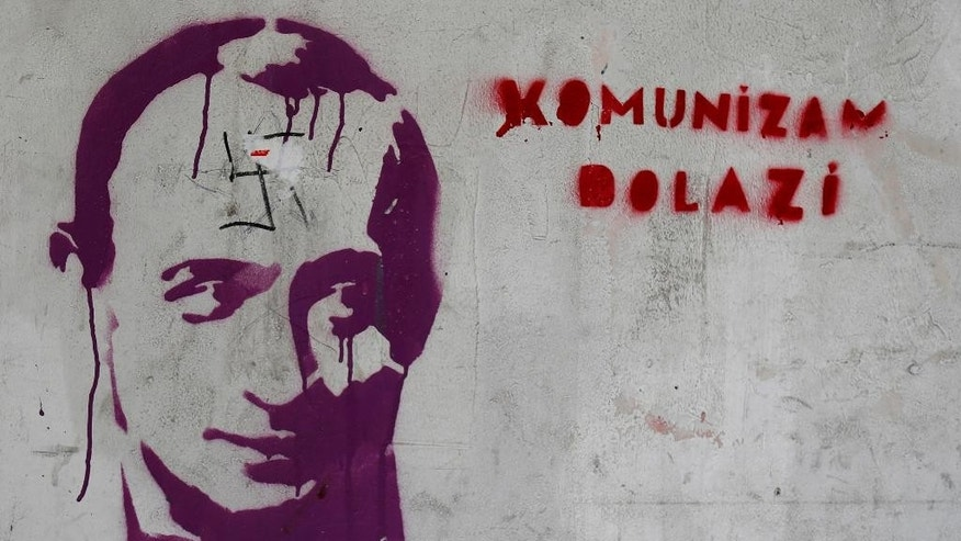 "In this photo taken Wednesday, Aug. 27, 2014, a graffiti that shows a picture of Russian President Vladimir Putin defaced with a Nazi swastika and text reading: ""Communism is coming"", on the wall in downtown Belgrade, Serbia. Serbia, caught in the middle of Moscow's row with the European Union and the United States over the crisis in Ukraine, is suddenly being confronted with a hard choice: continue on its proclaimed course toward the EU, or give up that goal and seek even closer ties with its traditional Slavic ally Russia. (AP Photo/Darko Vojinovic)"