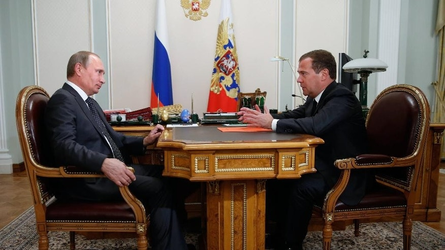 Russian President Vladimir Putin listens to Russian Prime Minister Dmitry Medvedev, right, at the Novo-Ogaryovo residence outside Moscow on Monday, Sept 8, 2014. (AP Photo/RIA Novosti, Dmitry Astakhov, Government Press Service)