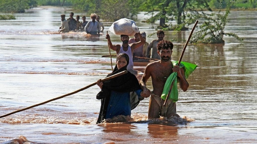 Pakistani villagers wade through water to find safe shelters in Pindi Bhatian, 105 kilometers (65 miles) northeast of Lahore, Pakistan, Monday, Sept. 8, 2014. Army and air force troops on Monday worked to rescue thousands of people stranded in Indian-controlled Kashmir and northern and eastern Pakistan, where flooding and landslides have caused hundreds of deaths. (AP Photo/K.M. Chaudary)