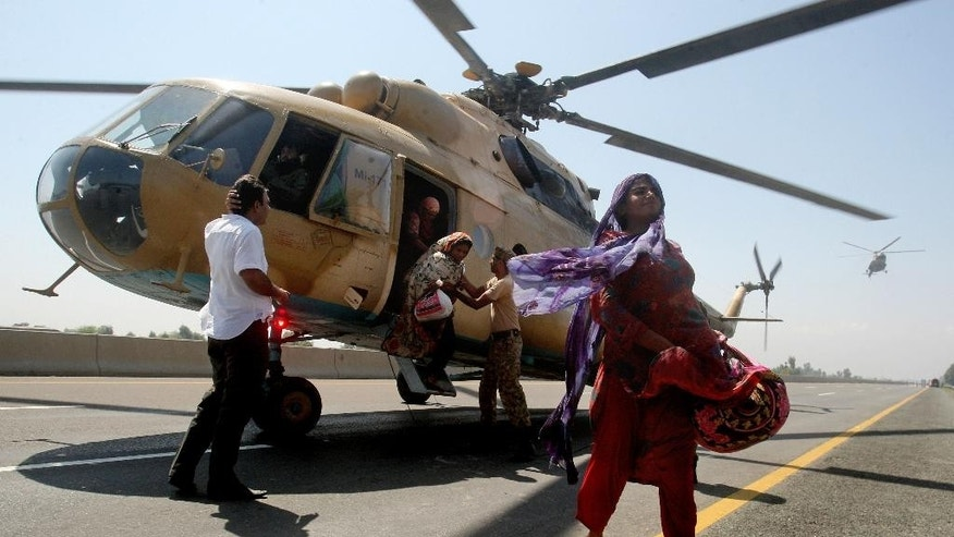 Pakistani villagers leave a helicopter after being rescued by army troops in Pindi Bhatian, 105 kilometers (65 miles) northeast of Lahore, Pakistan, Monday, Sept. 8, 2014. Army and air force troops on Monday worked to rescue thousands of people stranded in Indian-controlled Kashmir and northern and eastern Pakistan, where flooding and landslides have caused hundreds of deaths. (AP Photo/K.M. Chaudary)