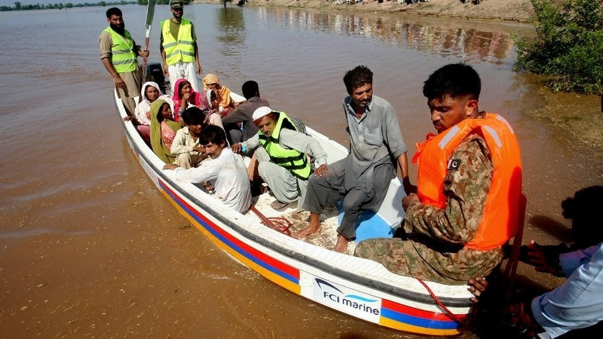 Pakistani soldiers and volunteers rescue villagers in Pindi Bhatian, 105 kilometers (65 miles) northeast of Lahore, Pakistan, Monday, Sept. 8, 2014. Army and air force troops on Monday worked to rescue thousands of people stranded in Indian-controlled Kashmir and northern and eastern Pakistan, where flooding and landslides have caused hundreds of deaths. (AP Photo/K.M. Chaudary)