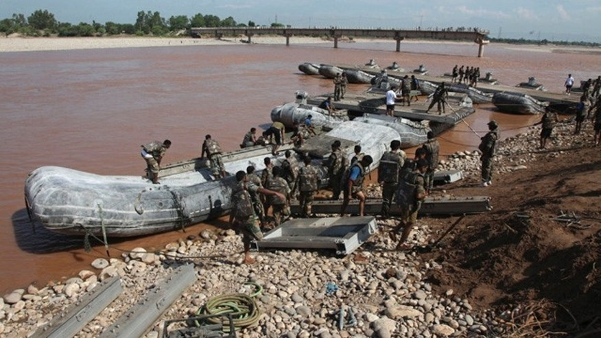 September 9, 2014: Indian army soldiers build a temporary bridge across the Tawi River after the existing bridge was damaged in the floods on the outskirts of Jammu, India. The flash floods, which began on Sept. 3, have killed hundreds, put more than half a million people in peril and rendered thousands homeless in India and Pakistan. (AP Photo/Channi Anand)