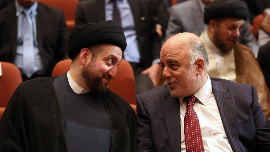 Iraq's new Prime Minister Haider al-Abadi, right, and Ammar al-Hakim, front, the leader of the Supreme Islamic Council of Iraq, left, during the session to approve the new government in Baghdad, Iraq, Monday, Sept. 8, 2014. Iraq's parliament officially named Haider al-Abadi the country's new prime minister late Monday and approved most of his proposed Cabinet amid calls by the Arab League for its members to combat the Sunni militant group violently advancing across Iraq and Syria.(AP Photo/Hadi Mizban, Pool)