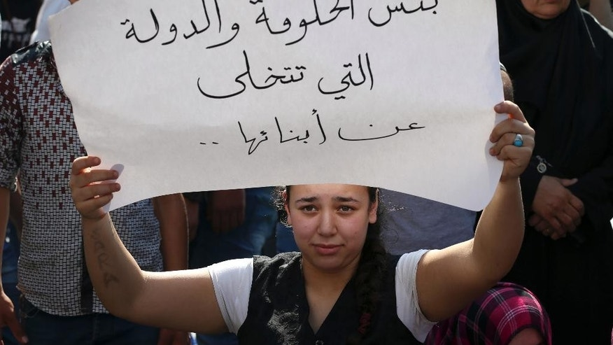 "A relative of a missing Lebanese soldier who was kidnapped by Islamic State militants holds an Arabic placard that reads: ""Shame on a government and nation that abandons its children,"" during a demonstration to demand action to secure the captives' release, in front the Lebanese government building, in downtown Beirut, Lebanon, on Thursday Sept. 4, 2014. Lebanon's government is forming a crisis committee to handle the case of some two dozen members of the security forces held captive by Syrian militants amid escalating criticism over its response to the hostage affair. Militants, including from the Islamic State extremist group, seized around 30 soldiers and policemen after overrunning a Lebanese border town in early August. (AP Photo/Hussein Malla)"